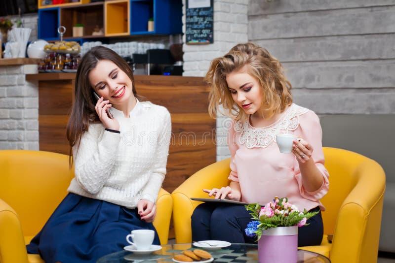 Zwei Mädchen, die Kaffee in einem Café trinken lizenzfreie stockfotos