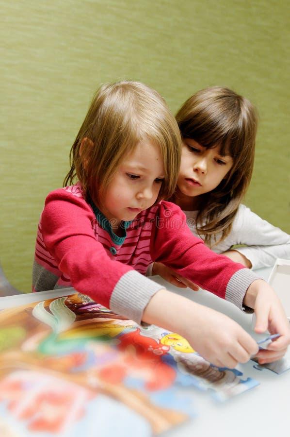 Zwei Mädchen, die Puzzlespiel tun lizenzfreie stockfotos
