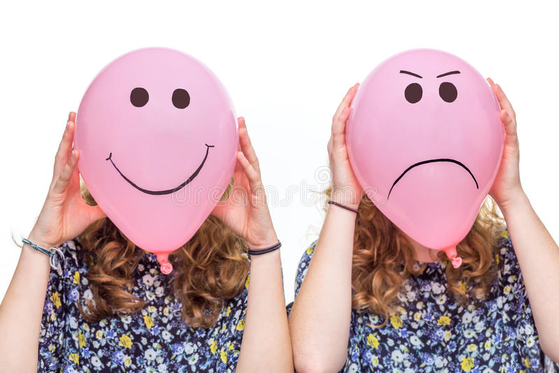 Zwei Mädchen, die rosa Ballone mit Gesichtsausdrücken für Kopf halten stockfotos