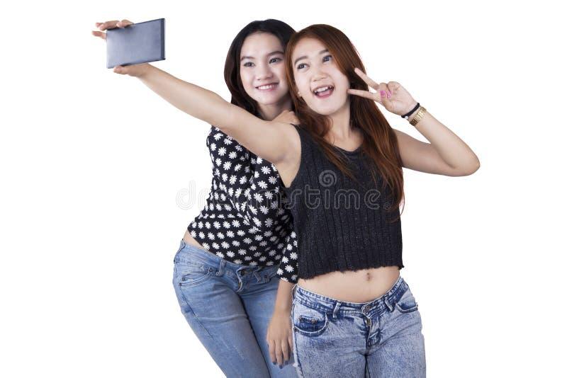 Zwei Mädchen, die selfie im Studio nehmen lizenzfreie stockfotos