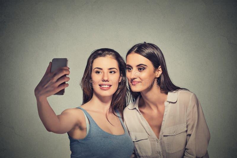 Zwei Mädchen, die selfie mit intelligenter Telefonkamera nehmen stockfotografie