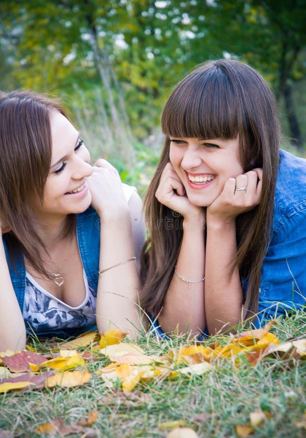 Zwei Mädchen, die Spaß nahe gelben Blättern haben stockfoto