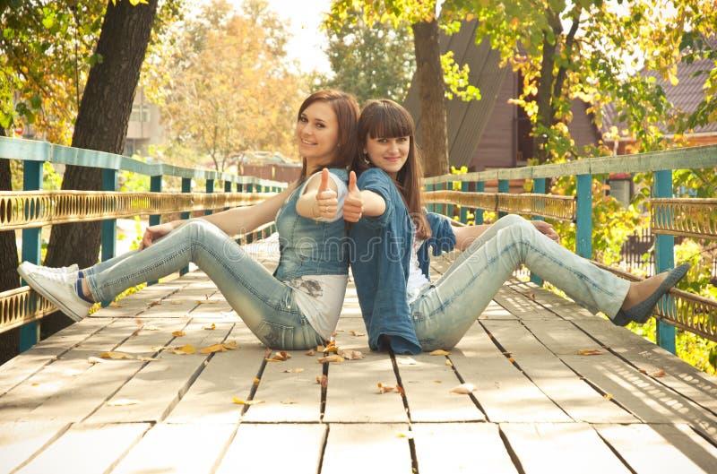 Zwei Mädchen, die Thumbs-up zeigen stockbild