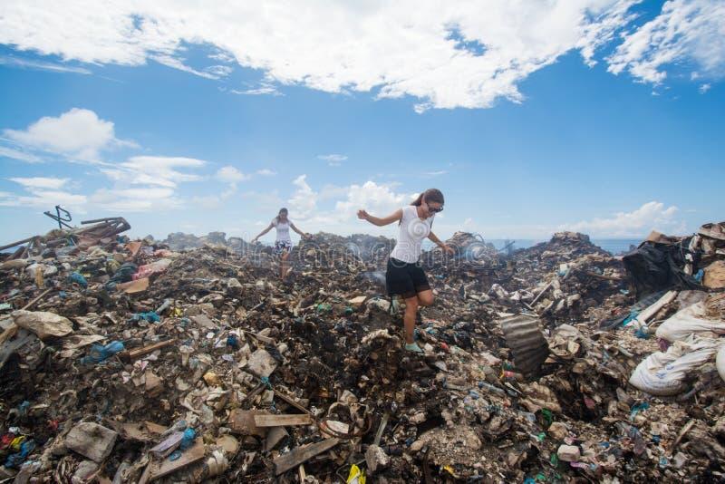 Zwei Mädchen, die unter Abfall an der Müllkippe gehen lizenzfreies stockfoto