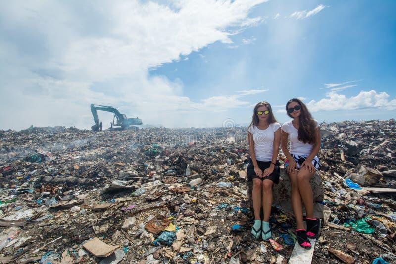 Zwei Mädchen, die unter Abfall an der Müllkippe sitzen stockbild