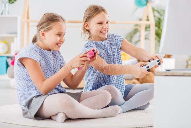 Zwei Mädchen, die Videospiele spielen stockfoto