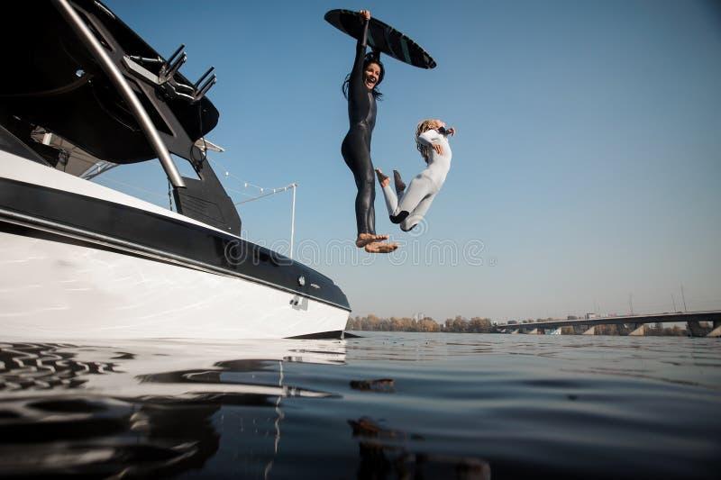 Zwei Mädchen, die zum Fluss mit wakeboard springen lizenzfreies stockbild