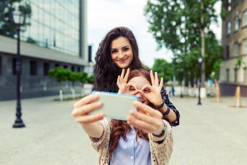 Zwei Mädchen, die zusammen lustiges selfie auf der Straße, Spaß habend machen stockbild