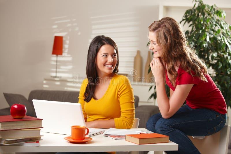 Zwei Mädchen, die zusammen am Tisch lachen stockfotografie
