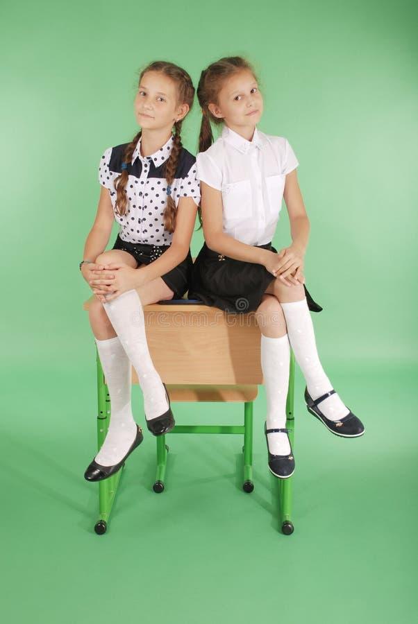 Zwei Mädchen in einer Schuluniform, die auf Schreibtisch sitzt lizenzfreies stockbild