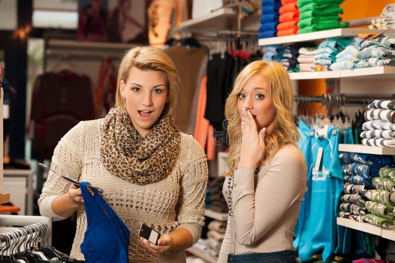 Zwei Mädchen entsetzt durch einen Preis von Kleidung in einem Shop lizenzfreie stockfotos