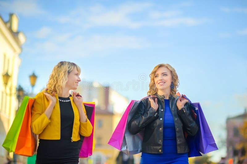 zwei Mädchen gehen hinunter und lächeln die Straße mit Einkaufstaschen lizenzfreies stockfoto