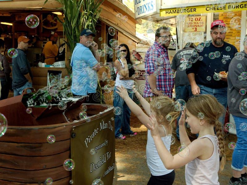 Zwei Mädchen greifen Luftblasen an, wenn Familie und Besucher zusehen stockfotos