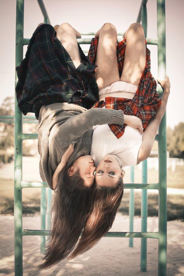 Zwei Mädchen hängen an einer horizontalen Stange in einer Umarmung Das Konzept von schwierigen Jugendlichen, schlechte Studenten lizenzfreie stockbilder