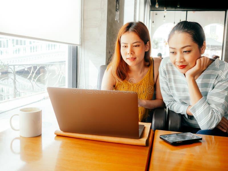 Zwei Mädchen haben etwas Spaß die Fotoarbeit heraus überprüfend im Laptop im Café lizenzfreies stockfoto