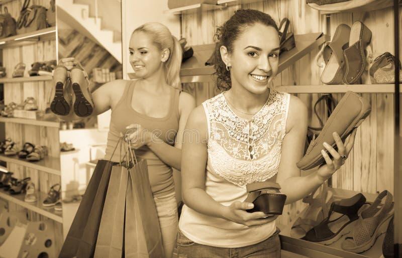 Zwei Mädchen, halten Papiereinkaufstaschen in der Butike stockfotografie