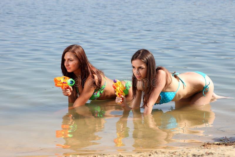 Zwei Mädchen im Bikini spielen mit Gewehren eines Wassers stockfoto