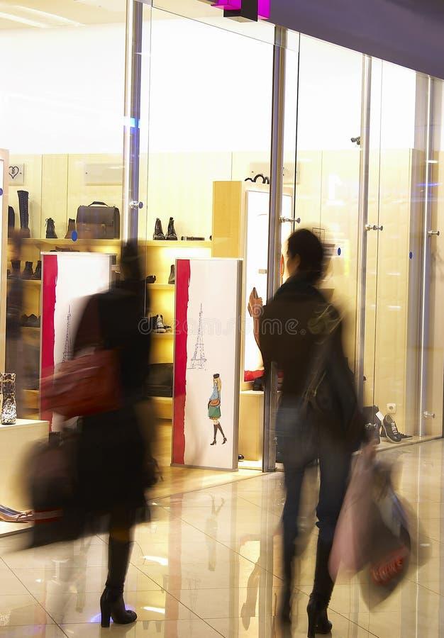Zwei Mädchen im Einkaufszentrum nahe einem Zeigenfenster des Systems stockfoto