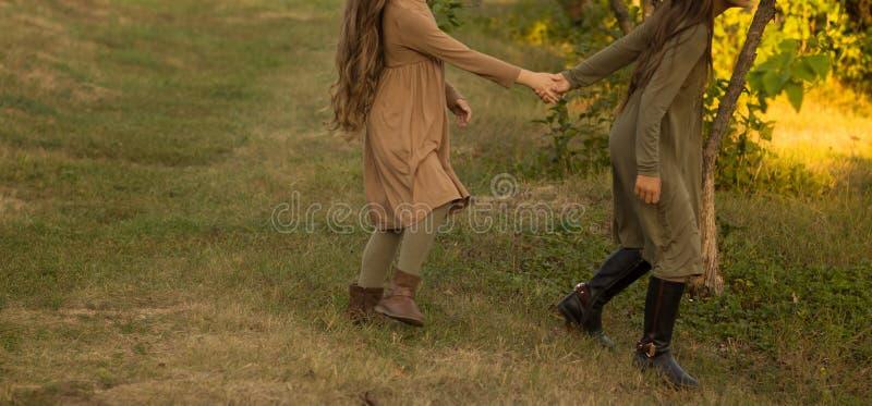 Zwei Mädchen, Jugendliche, Händchenhalten, Weg auf grünem Gras, Lauf in der Natur lizenzfreies stockfoto