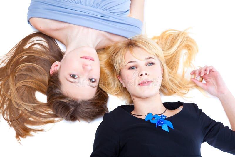 Zwei Mädchen liegt auf einem Fußboden lizenzfreie stockfotos