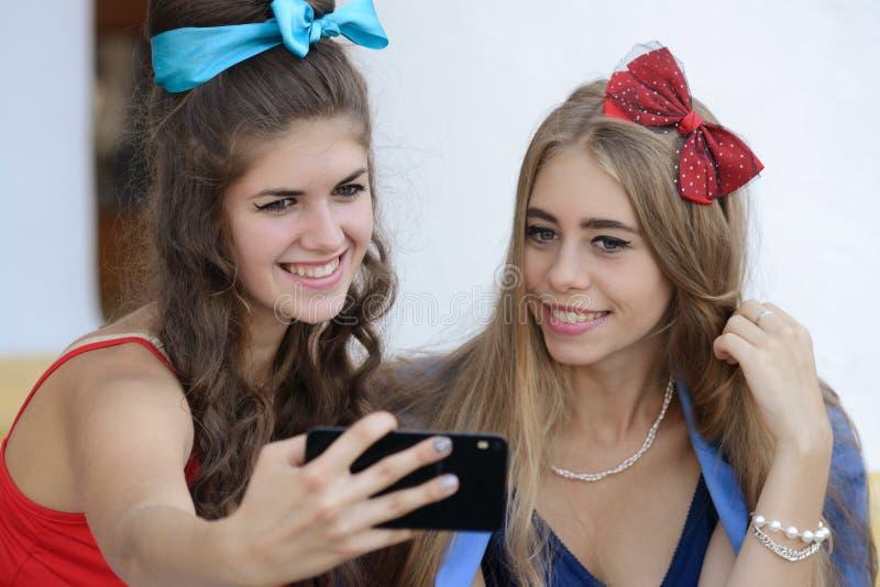 Zwei Mädchen machen Fotos an Ihrem Telefon lizenzfreies stockbild