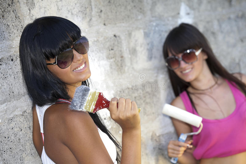 Zwei Mädchen mit Anstrichrolle und -malerpinsel stockfotografie