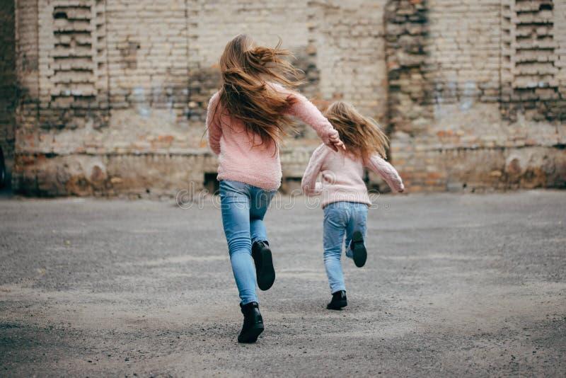 Zwei Mädchen mit dem langen Haar, das weg läuft lizenzfreie stockfotografie