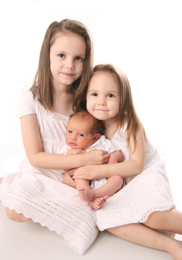 Zwei Mädchen mit neugeborener Schwester lizenzfreies stockbild