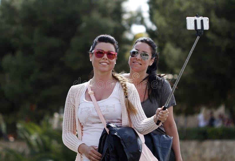 Zwei Mädchen nehmen ein selfie auf der Straße lizenzfreie stockfotos