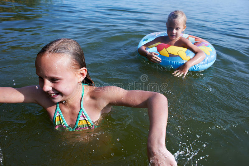 Zwei Mädchen schwimmen in einem See stockbilder