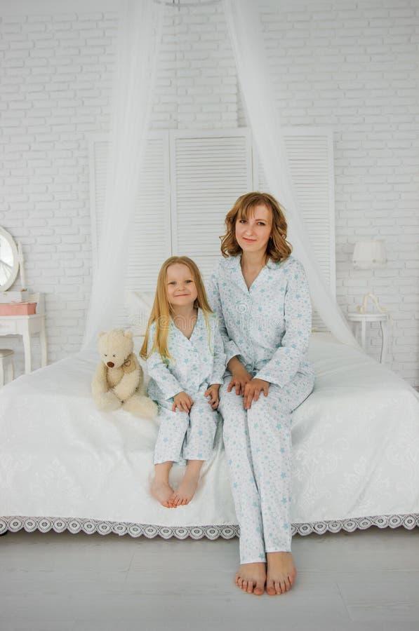 Zwei Mädchen sind auf dem Bett glücklich Mutter und Tochter sitzen auf dem Bett lizenzfreie stockbilder