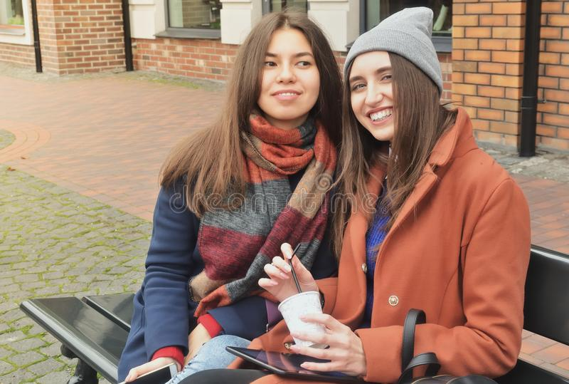 Zwei Mädchen sitzen auf der Bank und lächeln lizenzfreie stockfotos