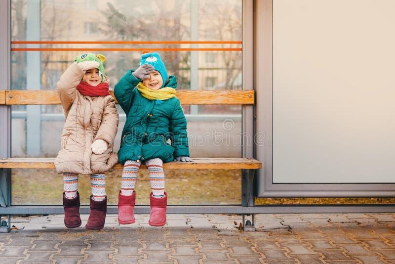 Zwei Mädchen sitzen an der Bushaltestelle stockfotografie