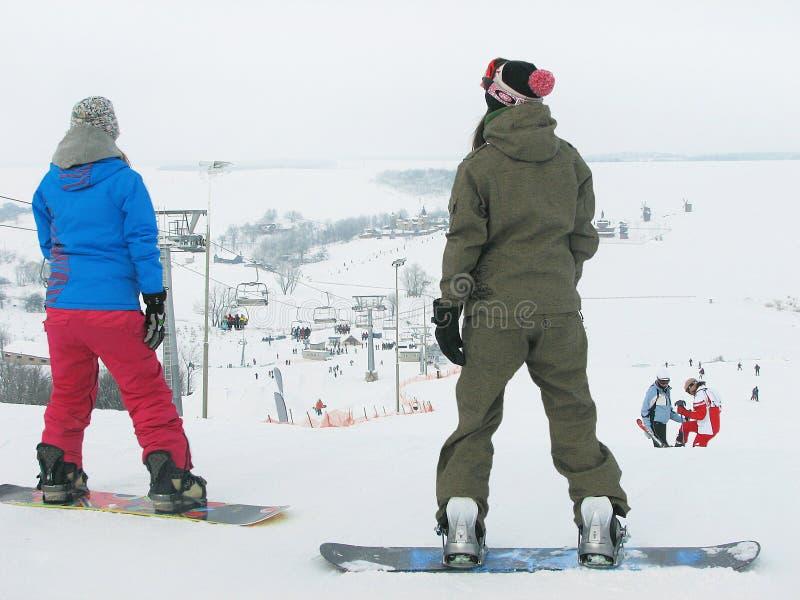 Zwei Mädchen (Snowboarder) stehen auf dem schneebedeckten Hintergrund stockbild