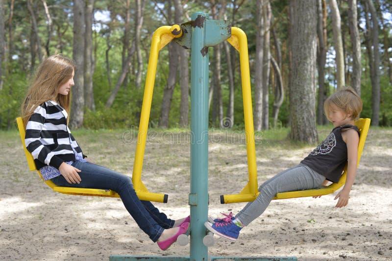 Zwei Mädchen spielen auf dem Spielplatz auf der gelbes Metallanziehungskraft Es ist windig lizenzfreies stockfoto