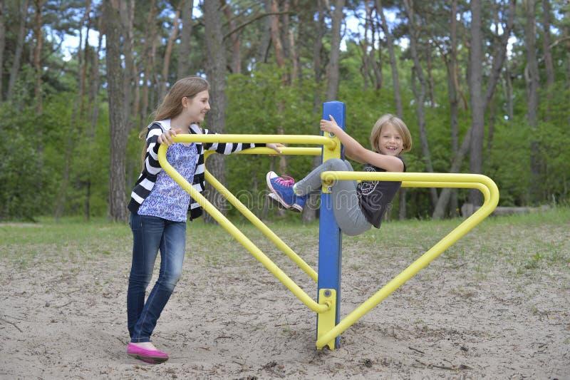 Zwei Mädchen spielen auf dem Spielplatz auf der gelbes Metallanziehungskraft Es ist windig stockfoto