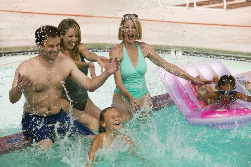 Zwei Mädchen (7-9) spielend mit Familie im Swimmingpool. lizenzfreie stockfotografie