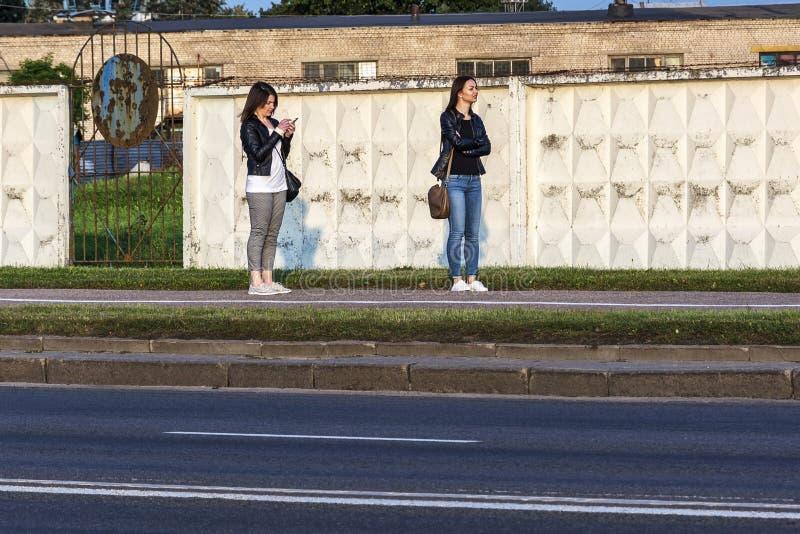 Zwei Mädchen stehen auf dem Bürgersteig nahe dem Zaun Minsk, sind lizenzfreie stockfotos