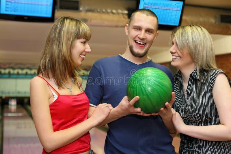 Zwei Mädchen und Mann stehen längsseits und lachen stockbild