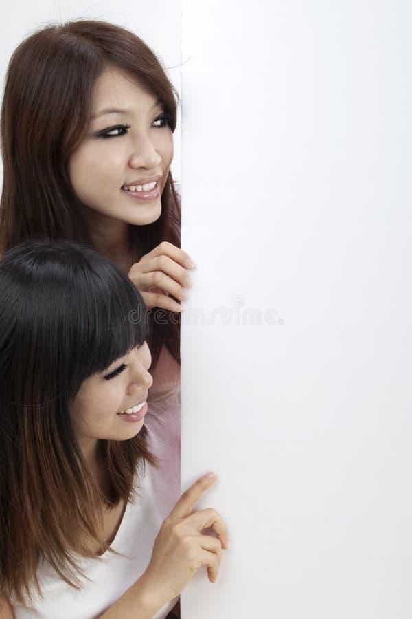Zwei Mädchen und unbelegtes Zeichen lizenzfreie stockfotos