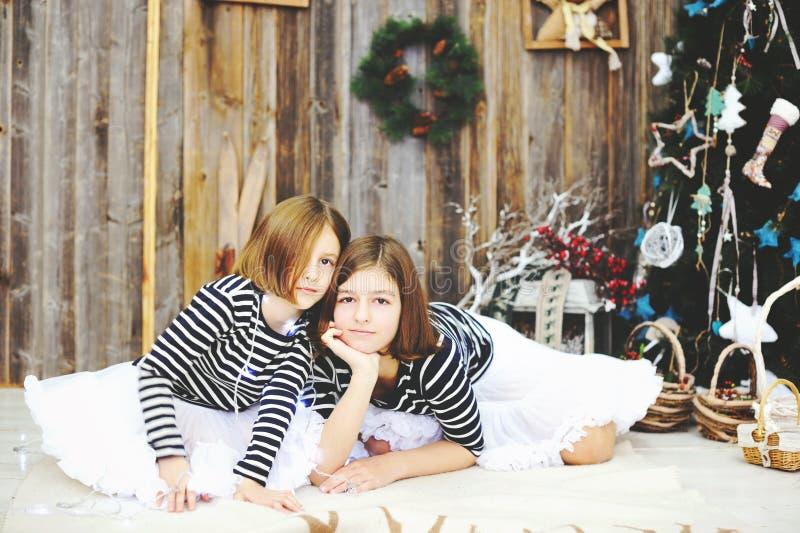Zwei Mädchen vor Weihnachtsbaum lizenzfreies stockbild