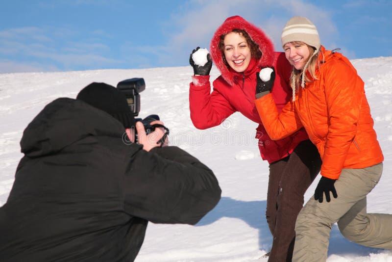Zwei Mädchen werfen Schnee in Fotografen lizenzfreie stockfotos