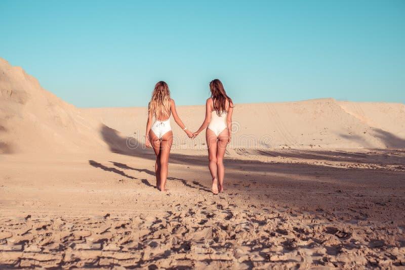 Zwei Mädchenfreundinnen, die Sandrückansicht gehen, Schönheiten nimmt weißer Bodysuit des Sommerstrandes ein Sonnenbad Restmeer a stockfotos
