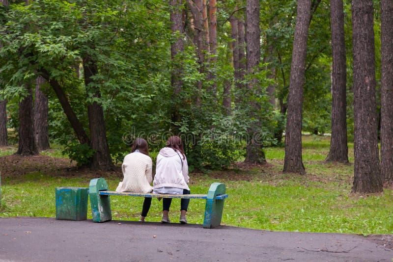 Zwei Mädchenfreundinnen sitzen auf einer alten Holzbank in einem Stadtpark und Blick an den Jahren mit grünen Bäumen bei der Disk stockfotografie