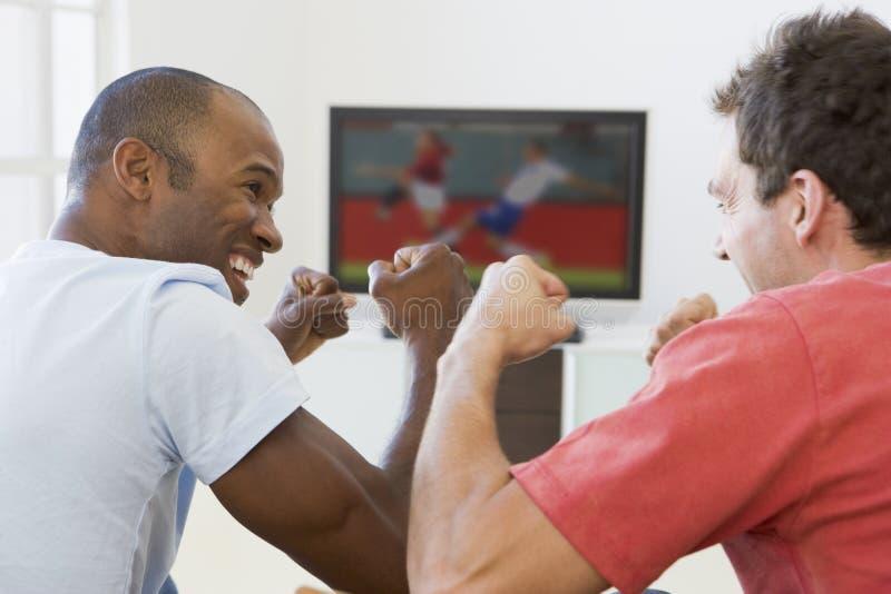 Zwei Männer in überwachendem Fernsehen des Wohnzimmers stockfoto