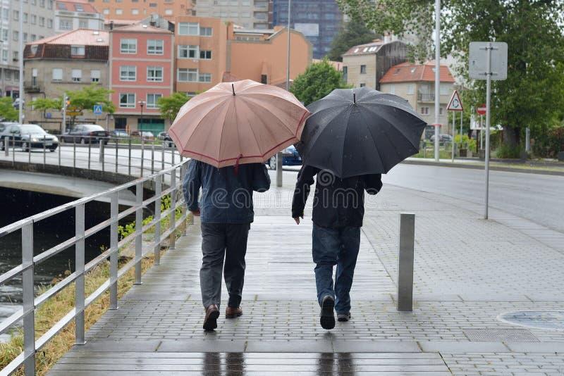 Zwei Männer auf der Straße mit Regenschirmen im Regen stockfoto