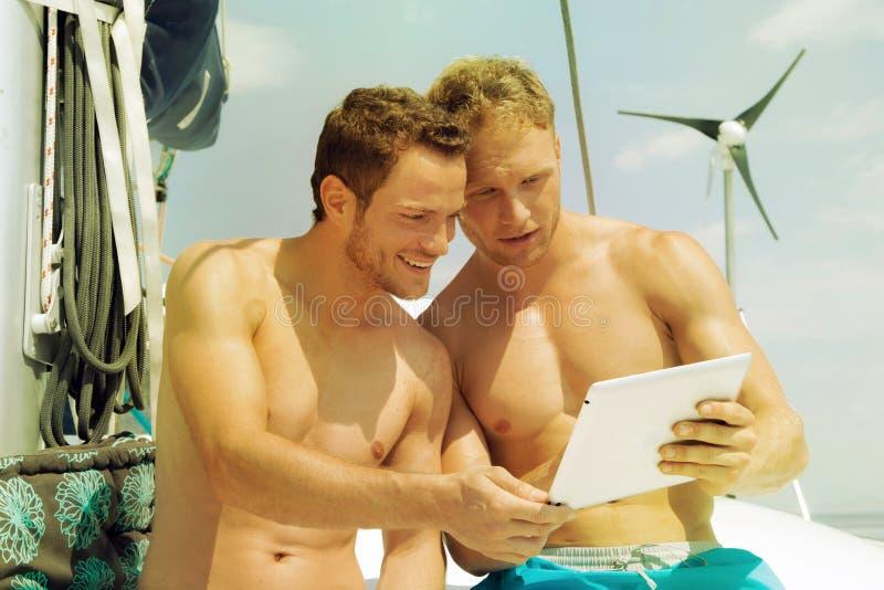 Zwei Männer auf einem Segelboot, das den Schirm einer Tablette betrachtet stockfotos