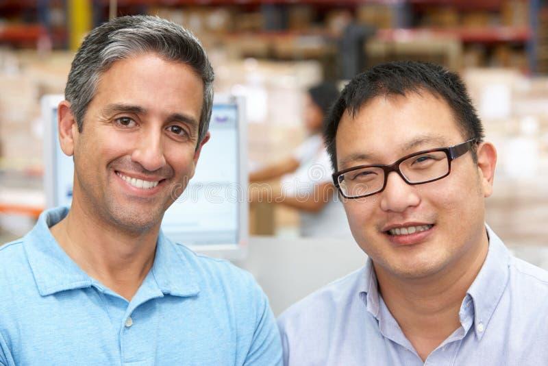 Zwei Männer am Computerterminal im Lagerhaus lizenzfreie stockfotografie