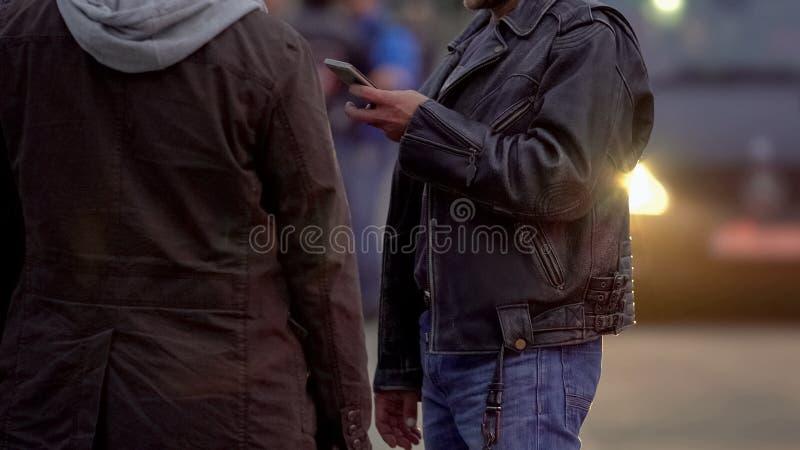 Zwei Männer in den Jacken bestellen Taxi im Freien, Wartedas Taxifahrer, um sie abzuholen stockbilder
