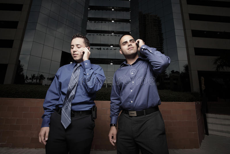Zwei Männer, die auf Mobiltelefonen sprechen lizenzfreies stockbild
